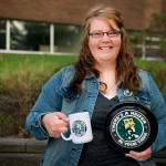 2012 winner Chelsea Geiger from Tawatinaw Alberta holding a There's a Heifer in Your Tank coffee mug.